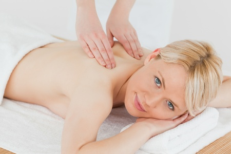 Closeup of young cute blonde woman receiving a back massage in a spa centre photo