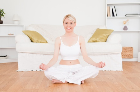 Delighted blonde woman practicing yoga at home photo