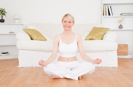 Attractive blonde woman practicing yoga at home Stock Photo - 10196498