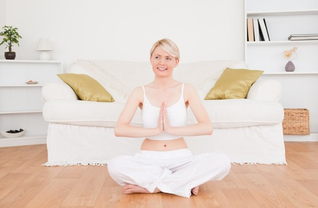 Pretty blonde woman practicing yoga at home photo