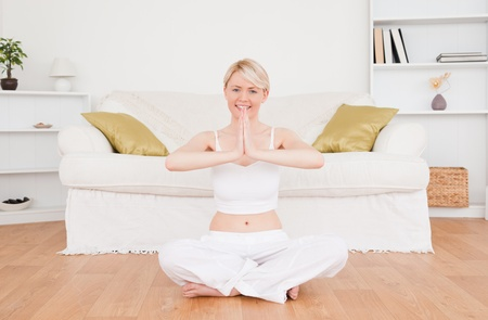 Pretty blond-haired woman practicing yoga at home photo