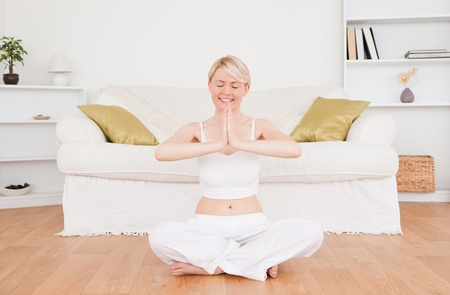 Beautiful blond-haired woman practicing yoga at home photo