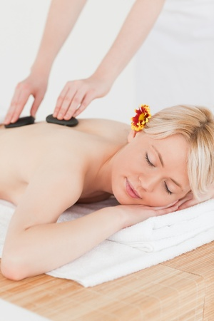 Pretty woman receiving a massage with hot stones in a Spa centre photo