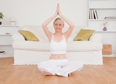 Cute blond-haired woman practicing yoga at home photo