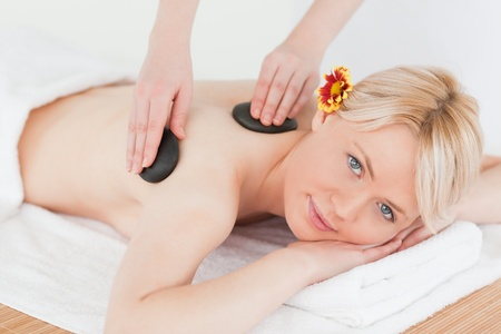 Cute woman receiving a massage with hot stones in a Spa centre photo