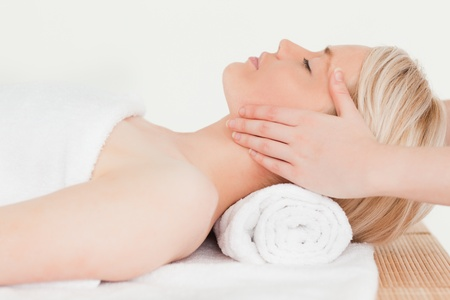 Blonde woman enjoying her treatment while lying down in a Spa centre photo