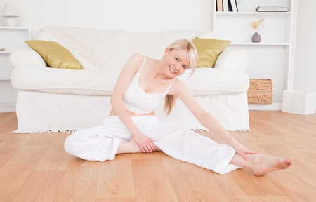 Happy woman doing fitness exercises in the living-room photo