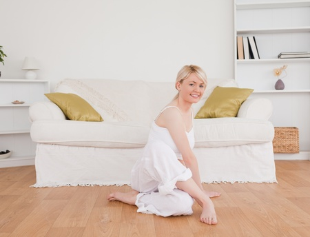 Cute woman doing fitness exercises in the living-room photo