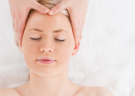 Delighted young woman getting a massage on her face in a Spa centre photo