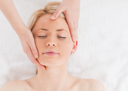 Cute young woman getting a massage on her face in a Spa centre photo