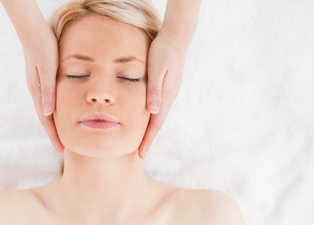 Delighted blond-haired woman getting a massage on her face in a Spa centre photo
