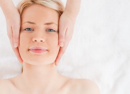 Happy blond-haired woman getting a massage on her face in a Spa centre photo