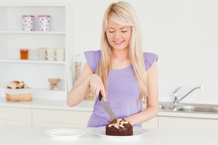 Smiling blonde female cutting a cake in a plate in the kitchen photo