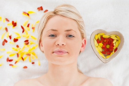 Attractive blonde woman lying down near flower petals in a Spa centre Stock Photo - 10196517