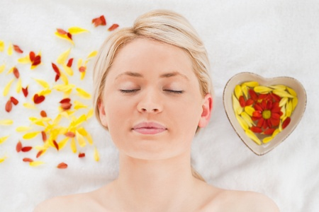Delighted blonde woman lying down near flower petals in a Spa centre photo