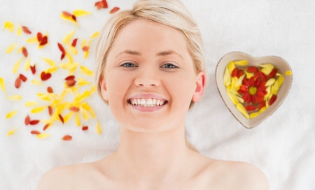 Cute woman lying down near flower petals in a Spa centre photo