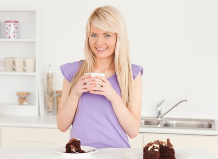 Smiling blonde woman eating cake and drinking coffee in the kitchen photo