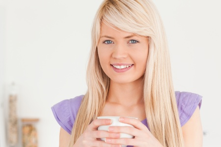 Beautiful female drinking hot drink in the kitchen photo