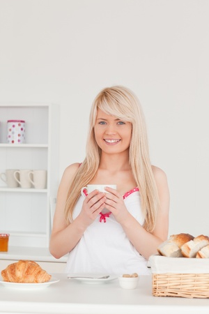 Beautiful blonde woman having her breakfast in the kitchen in her appartment photo