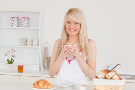 Attractive blonde woman having her breakfast in the kitchen in her appartment photo
