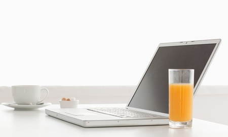 Modern and stylish laptop on a table while breakfast time in the kitchen photo