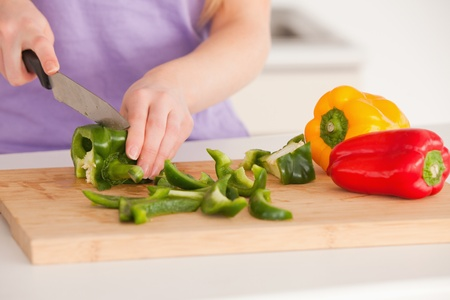 Woman cutting vegetables in modern kitchen interior in her appartment photo