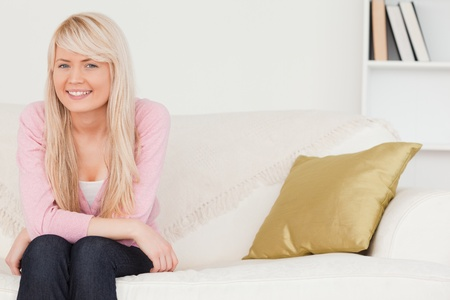 Attractive blonde woman posing while sitting on a sofa in the living room photo
