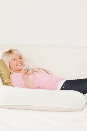 Good looking blonde female posing while lying on a sofa in the living room photo