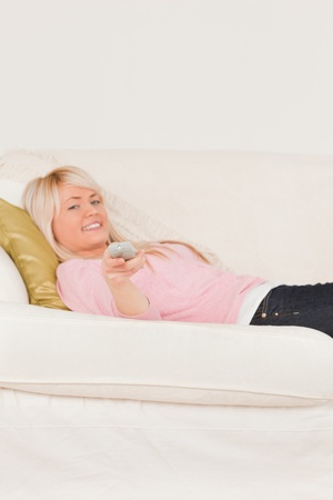 Good looking blonde woman posing while lying on a sofa in the living room photo