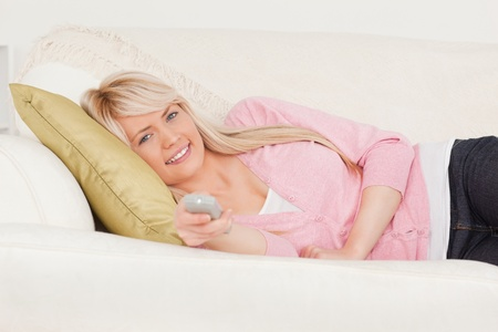 Attractive blonde female posing while lying on a sofa in the living room Stock Photo - 10206221