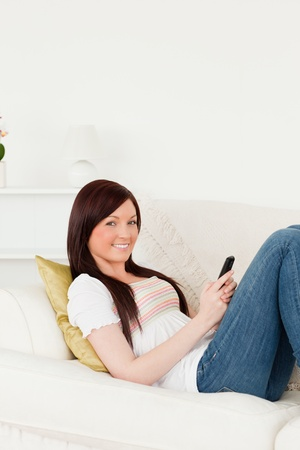 Attractive red-haired woman writing a text on her phone while lying on a sofa in the living room photo