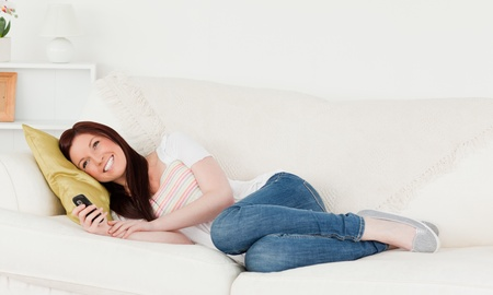 Pretty red-haired woman writing a text on her phone while lying on a sofa in the living room photo