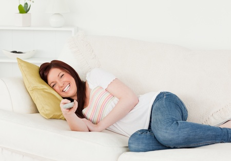 Good looking red-haired woman watching tv while lying on a sofa in the living room photo