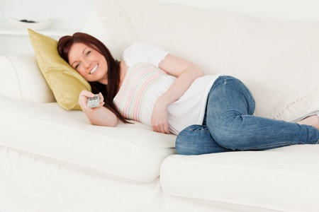 Beautiful red-haired woman watching tv while lying on a sofa in the living room photo