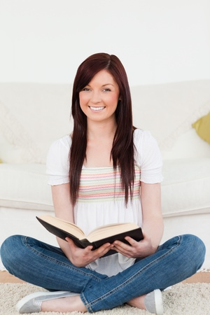 Good looking red-haired woman reading a book while sitting on a sofa in the living room Stock Photo - 10076000