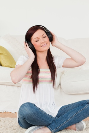 Attractive red-haired woman listening to music with headphones while sitting on a carpet in the living room photo