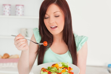 Charming red-haired woman enjoying a mixed salad in the kitchen in her appartment photo