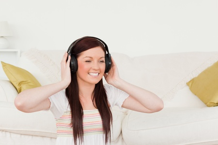 Gorgeous red-haired woman listening to music with headphones while sitting on a carpet in the living room photo