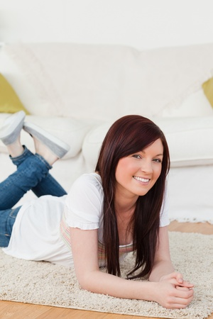 Good looking red-haired woman posing while lying on a carpet in the living room Stock Photo - 10069534