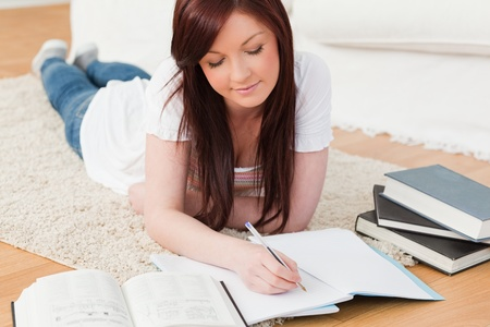 Beautiful joyful red-haired girl studying for while lying on a carpet in the living room Stock Photo - 10076002