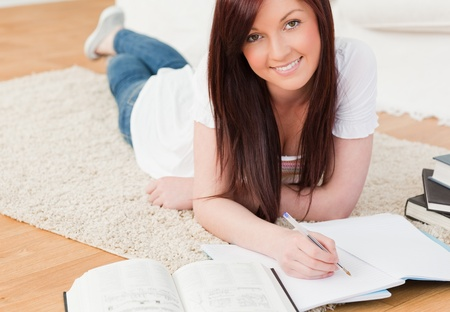 Attractive red-haired girl studying for while lying on a carpet in the living room Stock Photo - 10069520