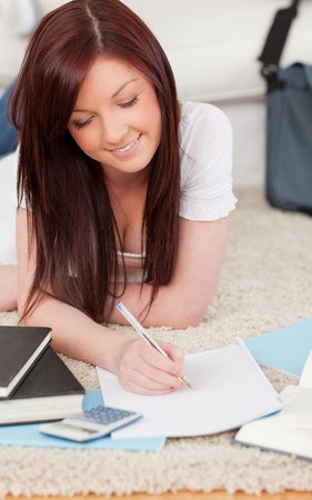 Cute red-haired female studying for while lying on a carpet in the living room Stock Photo - 10069454