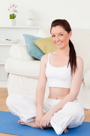 Young woman posing while sitting on a gym carpet in the living room Stock Photo - 10068826