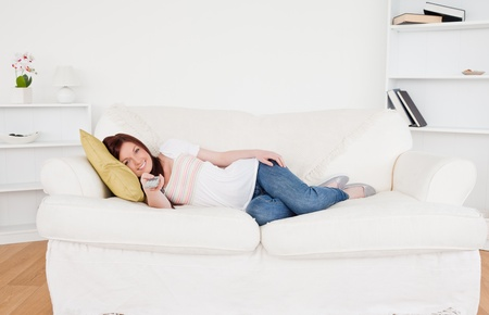 Beautiful red-haired female watching tv while lying on a sofa in the living room photo