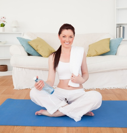Smiling female having a rest after stretching while sitting on a gym carpet in the living room photo