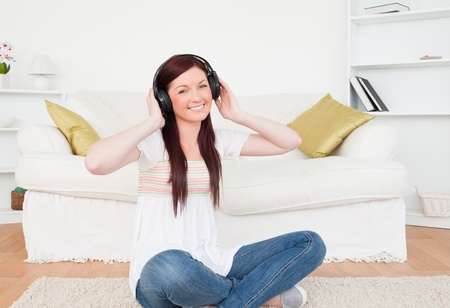 Attractive red-haired female listening to music with headphones while sitting on a carpet in the living room photo