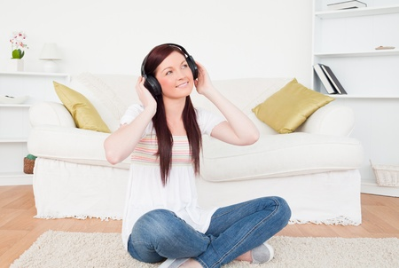Good looking red-haired female listening to music with headphones while sitting on a carpet in the living room photo