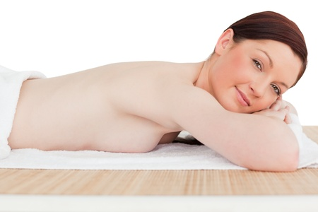 Young pretty red-haired female relaxing in a spa centre photo