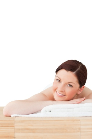 Smiling red-haired woman posing while relaxing in a spa centre photo