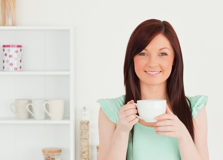 Charming red-haired woman having her breakfast in the kitchen in her appartment photo
